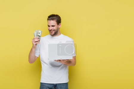 pleased man looking at dollars while holding laptop on yellow