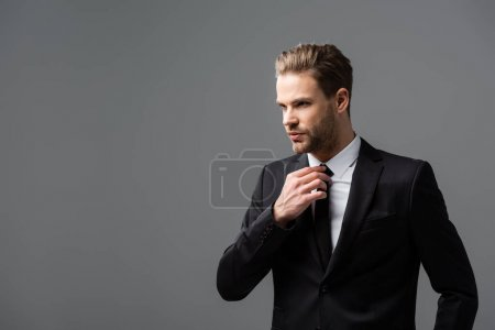 successful businessman looking away while touching tie isolated on grey