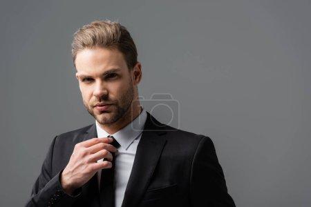 Foto de Serio hombre de negocios tocando la corbata mientras mira la cámara aislada en gris - Imagen libre de derechos