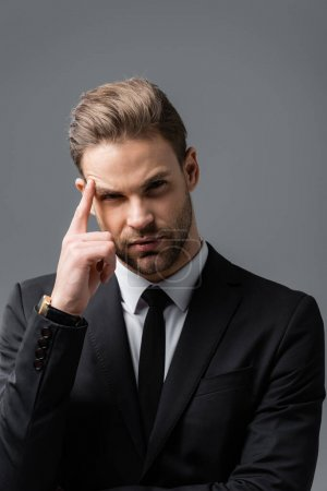 thinking businessman touching head and looking at camera isolated on grey