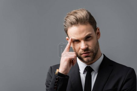 young, thoughtful businessman looking at camera while touching head isolated on grey