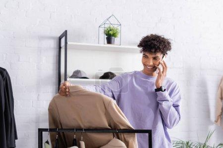 Photo pour Propriétaire afro-américain de showroom parlant sur smartphone et regardant chemise - image libre de droit