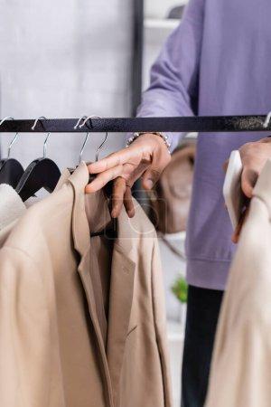 Photo pour Vue recadrée du propriétaire d'un showroom afro-américain tenant un smartphone près de vêtements sur des cintres - image libre de droit