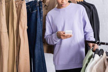 Photo pour Vue recadrée du propriétaire afro-américain du showroom en utilisant un smartphone près des vêtements - image libre de droit
