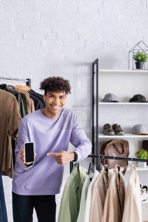 Photo pour Souriant propriétaire afro-américain de showroom pointant vers smartphone près des vêtements - image libre de droit
