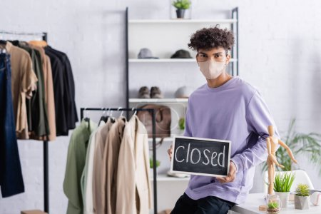 Photo for African american owner of showroom in protective mask holding chalkboard with closed lettering during quarantine - Royalty Free Image