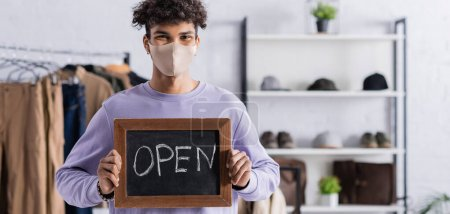 African american owner of showroom in protective mask holding chalkboard with open lettering, banner