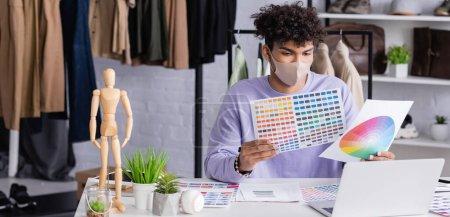Afroamerikanischer Showroom-Besitzer in Schutzmaske mit Blick auf Farbmuster in der Nähe von Laptop, Banner