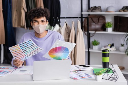African american owner of showroom in protective mask holding color swatches near gadgets and thermo cup
