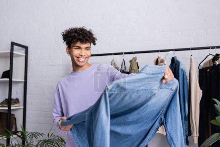 Photo pour Joyeux propriétaire afro-américain de showroom tenant cintre avec chemise en denim au premier plan flou - image libre de droit