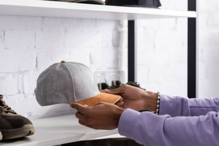 Cropped view of african american owner of showroom holding cap near shoe on shelf