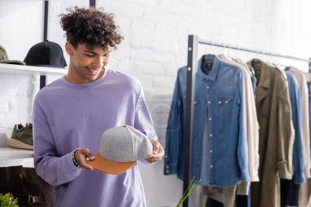 Photo pour Joyeux homme d'affaires afro-américain tenant chapeau dans le showroom - image libre de droit