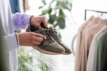Photo pour Vue recadrée du propriétaire afro-américain d'un showroom tenant des baskets près de vêtements sur fond flou - image libre de droit