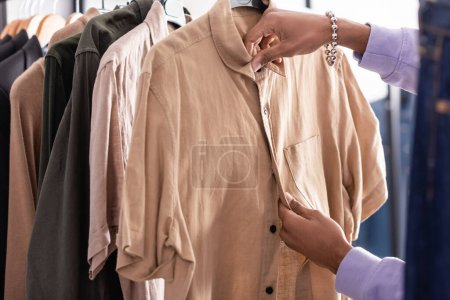 Cropped view of african american businessman fixing shirt on hanger in showroom
