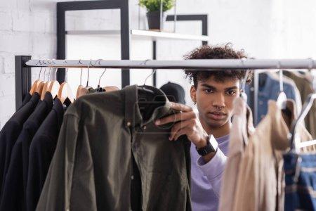 Afroamerikanisch-amerikanischer Showroom-Besitzer arbeitet mit Kleidern auf Hängeständer im verschwommenen Vordergrund