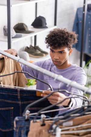 Young african american owner of showroom looking at jeans on hanging rack on blurred foreground