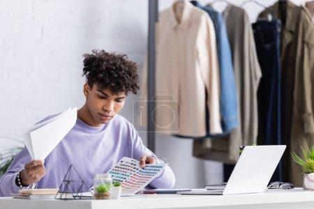 Afroamerikanischer Showroom-Besitzer hält bunte Armbanduhren in der Nähe von Laptop