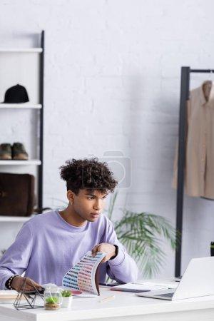 Junger afrikanisch-amerikanischer Showroom-Besitzer hält bunte Armbanduhren in der Hand und schaut auf Laptop