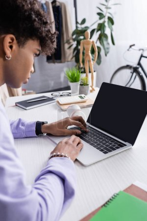 Portátil con pantalla en blanco cerca de hombre de negocios afroamericano en primer plano borroso trabajando en sala de exposición
