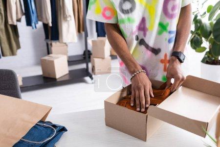 Photo pour Vue recadrée du jeune propriétaire d'un showroom afro-américain mettant des vêtements dans une boîte près d'un sac à provisions sur une table - image libre de droit