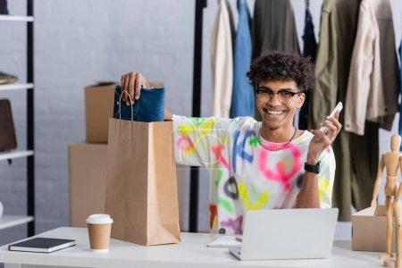 Alegre propietario afroamericano showroom celebración de teléfonos inteligentes y poner ropa en bolsa de compras