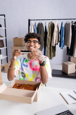 Smiling african american owner of showroom taking photo on smartphone near box with clothes and notebook