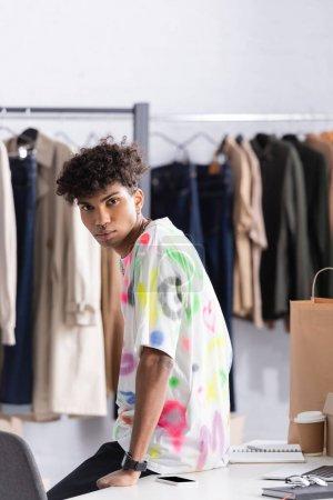 Photo pour Propriétaire afro-américain du showroom regardant la caméra près du smartphone, du café à emporter et du sac à provisions - image libre de droit
