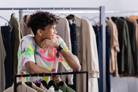 Photo pour Élégant propriétaire afro-américain de magasin de vêtements debout près de rack suspendu - image libre de droit