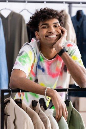 Photo pour Souriant propriétaire de showroom afro-américain regardant la caméra près des vêtements - image libre de droit