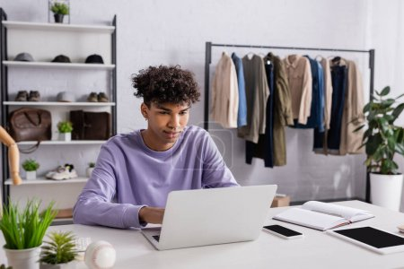 Young african american showroom owner working on laptop near devices and notebook