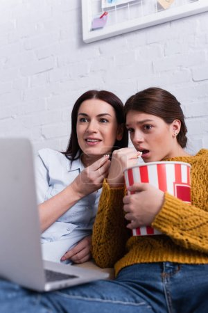 shocked teenage girl and mother watching movie on laptop in bedroom