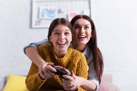 KYIV, UKRAINE - NOVEMBER 20, 2020: happy teenage girl holding joystick while playing video game with mother