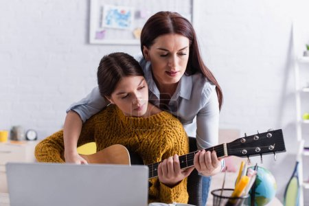 mother assisting teenage girl playing acoustic guitar near laptop