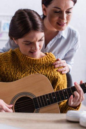 Photo pour Adolescent fille mordre lèvres tout en apprenant à jouer de la guitare acoustique près de mère - image libre de droit