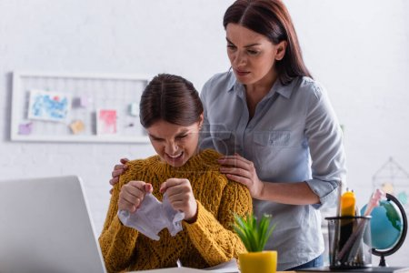 Photo pour En colère adolescent fille déchirure papier près inquiet mère - image libre de droit