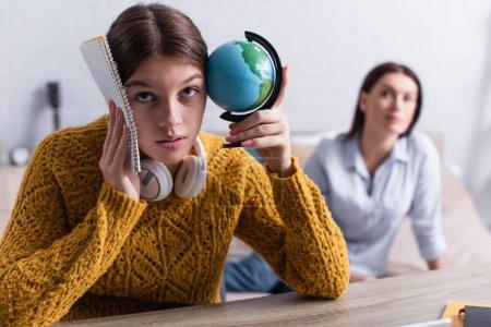 Photo pour Adolescente dans un casque sans fil tenant globe et ordinateur portable tout en roulant les yeux près de mère floue sur fond - image libre de droit