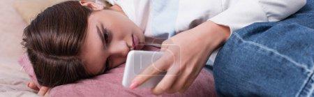 triste adolescente acostado en la cama y el uso de teléfono inteligente, pancarta