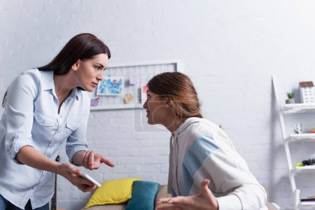 Mutter zeigt bei Streit mit beleidigter Tochter mit Finger auf Smartphone