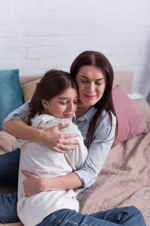 Photo pour Mère attentionnée embrassant fille adolescente dans la chambre - image libre de droit
