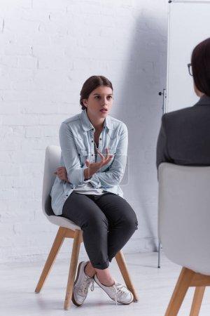 adolescente preocupada sentada y haciendo gestos mientras mira al psicólogo en primer plano borroso