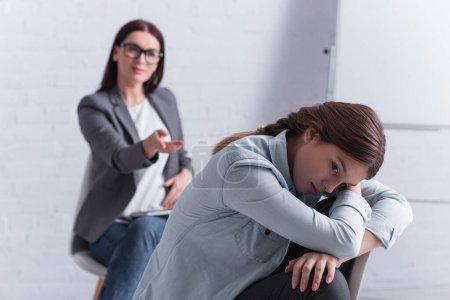 Photo pour Adolescent frustré regardant loin avec psychologue assis derrière sur fond flou - image libre de droit