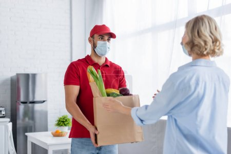 Photo for Back view of woman taking fresh food from arabian courier in medical mask on blurred foreground - Royalty Free Image