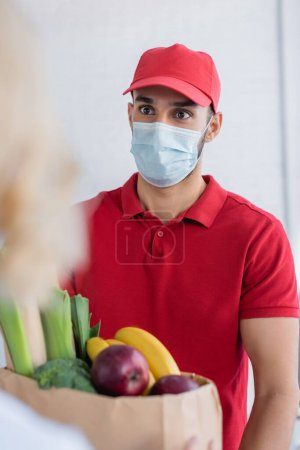 Photo for Young arabian delivery man in medical mask holding paper bag with fresh food near woman on blurred foreground - Royalty Free Image