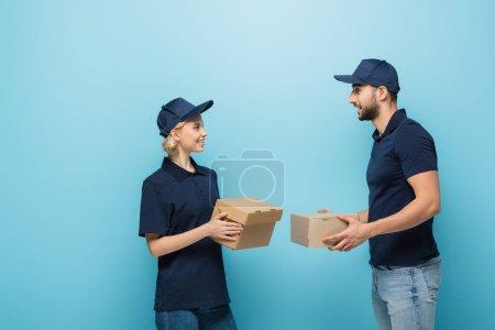 Photo pour Joyeux messagers multiculturels tenant des boîtes en carton tout en se regardant isolés sur bleu - image libre de droit