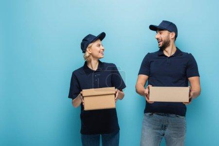 Photo pour Joyeux coursiers multiculturels qui se sourient tout en tenant des boîtes en carton sur bleu - image libre de droit