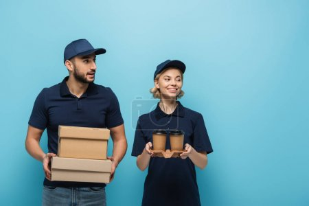 Photo for Smiling interracial couriers looking away while holding coffee to go and carton boxes isolated on blue - Royalty Free Image