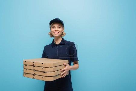 happy courier in uniform holding pizza boxes and smiling at camera isolated on blue