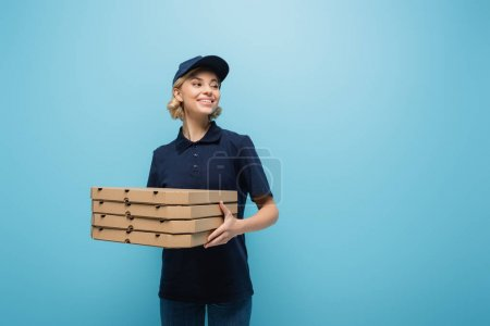 Photo for Pretty courier holding pizza boxes while looking away isolated on blue - Royalty Free Image