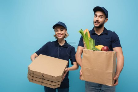 Photo for Cheerful interracial couriers with pizza boxes and paper bag with food isolated on blue - Royalty Free Image