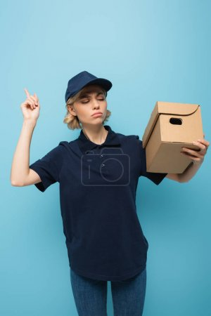 serious courier holding parcel and pointing up with finger on blue
